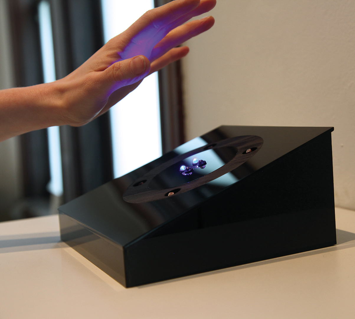 The system of reward, through LED luminosity, indicates to users that their interaction is indeed changing the audio they are hearing, and enables the user to intuit the necessary movement downward, closer to the face of the box, in order to complete the interaction.