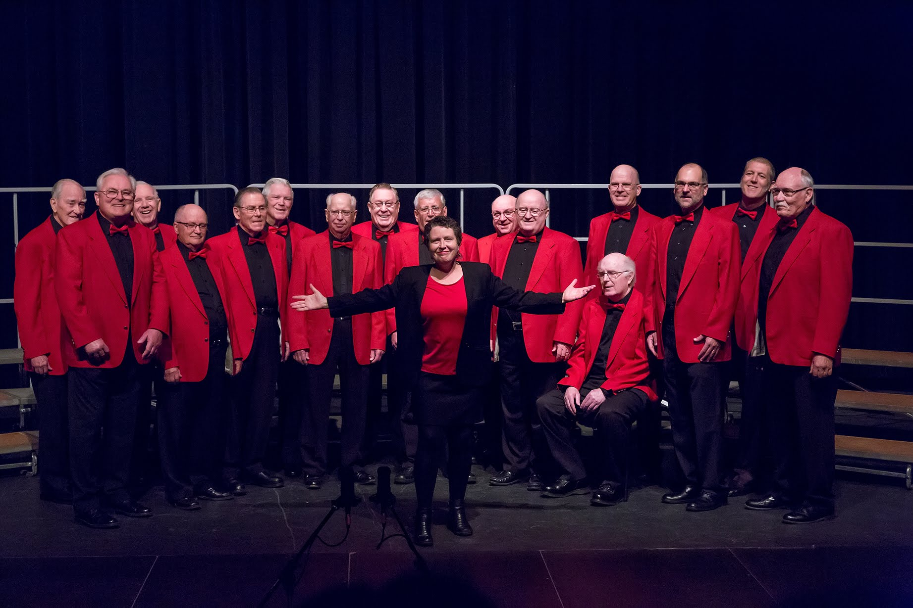 The chorus receiving the appreciation of the audience at the end of their performance.  L to R: George Smith, Tim Curry, Harry Cross, Glen Cosman, Bob Ellis, Dave Hansen, Al McPherson, Duncan Mugford, Rod Graham, Ken Creighton, John Wright, Mark McGillivray (seated), André Welland, Grant Clark, Mike Brown, John Backa.  Standing in front is Director Janet Kidd.