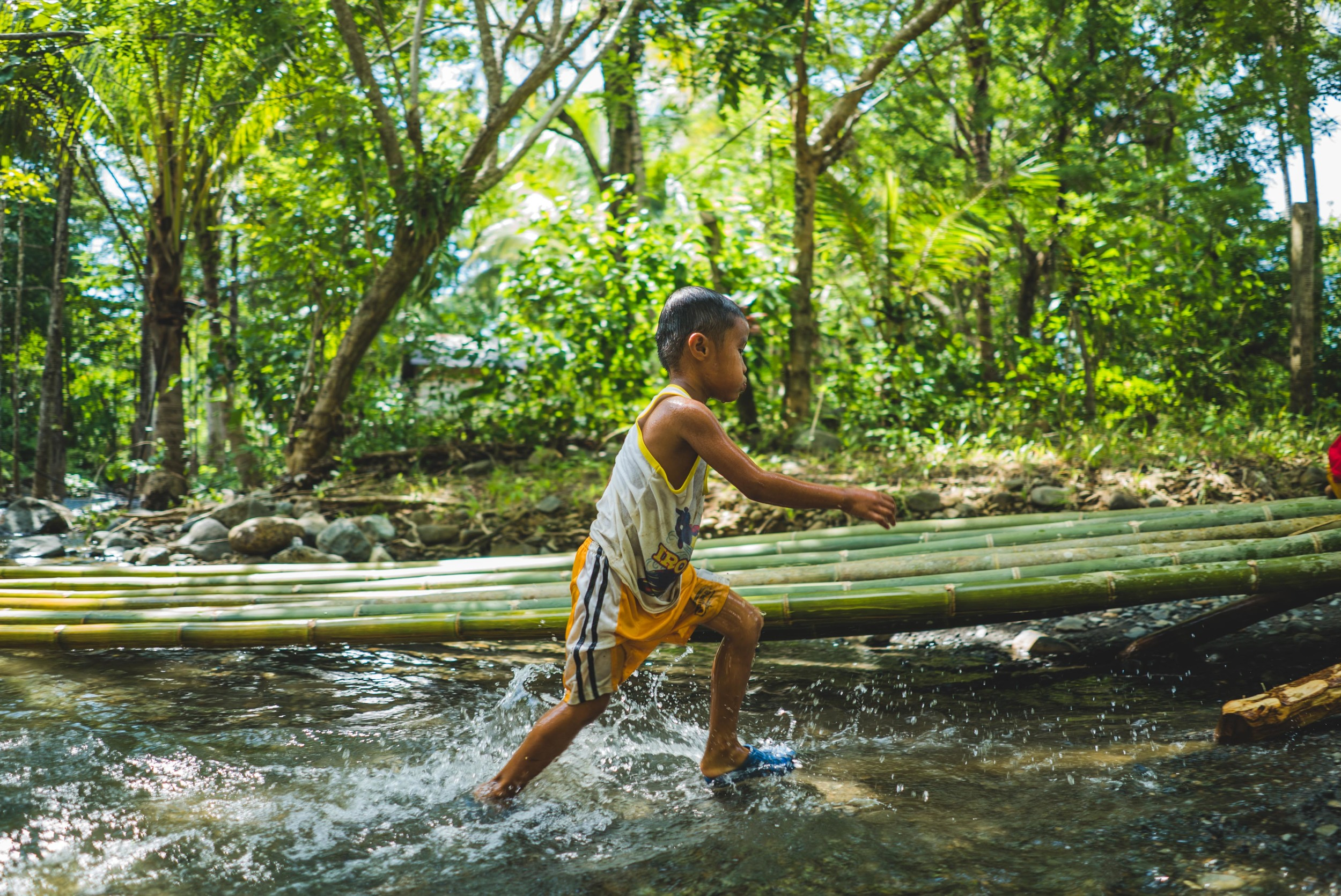A child splashes around to cool off as he runs through the river.