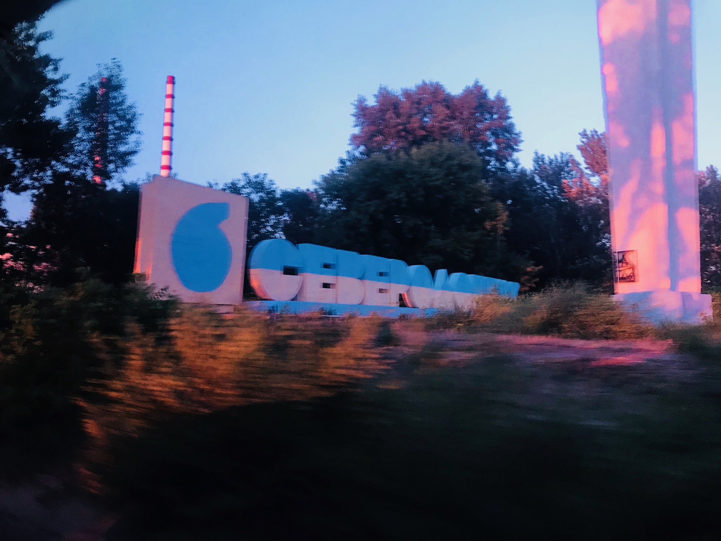 Highway sign at the entrance to the city of Severodonetsk, with AZOT Chemical Factory smokestack