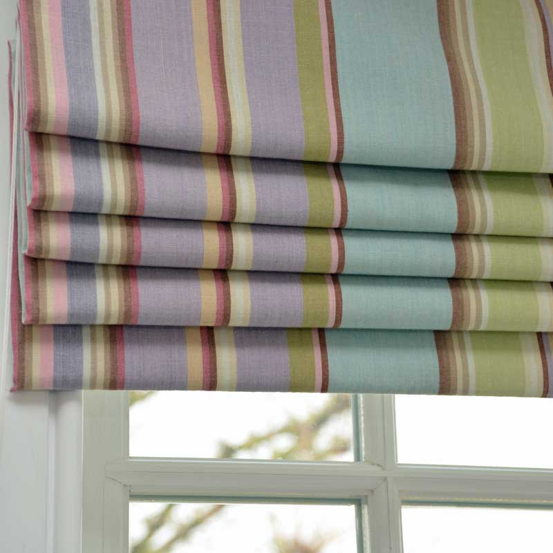 Vertically striped roman blinds in pastel pinks, purple and greens, drawn midway up a window.