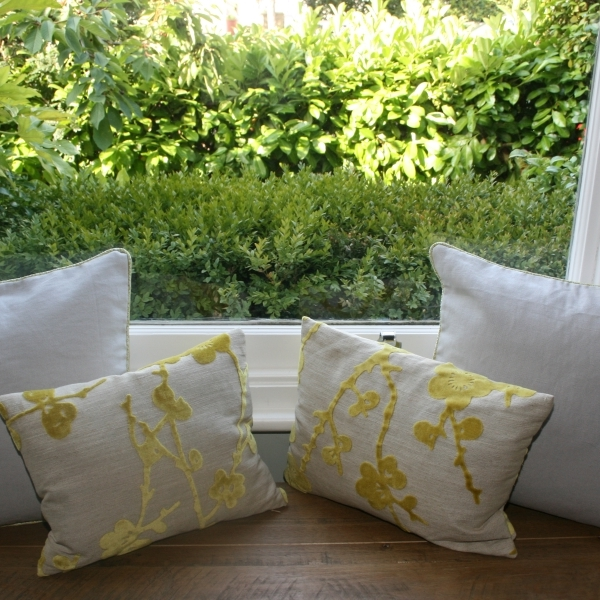 Two small rectangular cusions upholstered in cream fabric with mustard yellow flower patterns sit on a wooden window seat in front of a window. Vivid green shrubbery is seen behind.