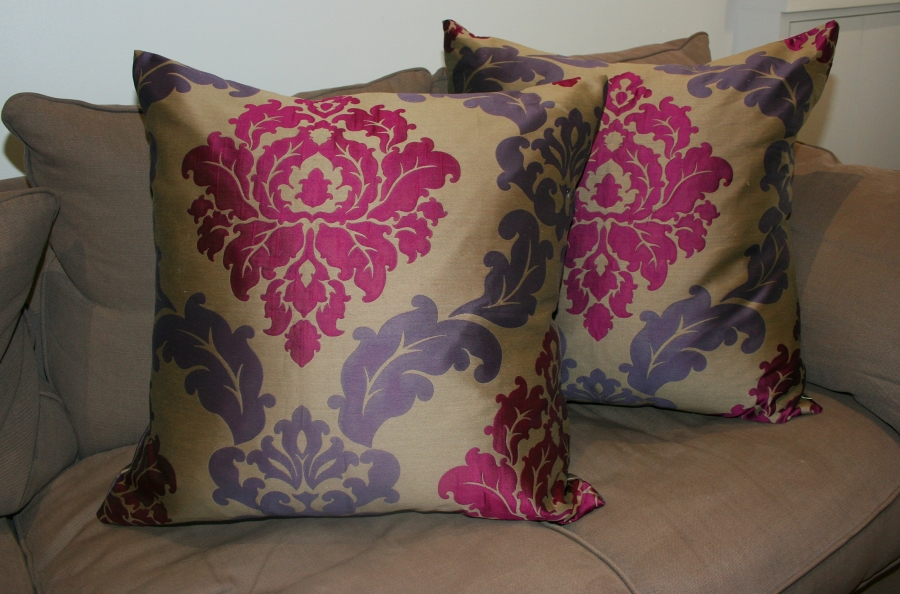 Two cushions, upholstered in an ornate pink and purple fabric