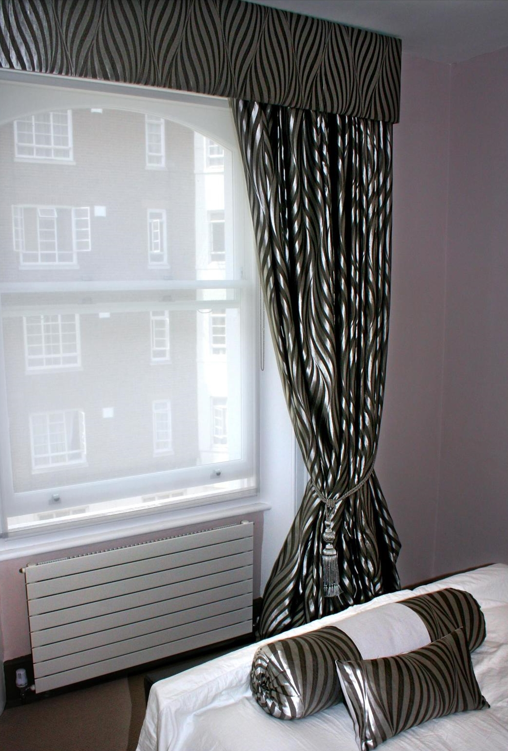 Full-length blackout blinds in a shiny, black and grey, zebra-print fabric