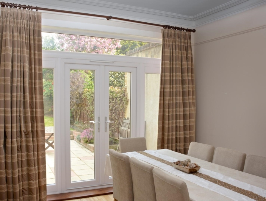 Full-length, double-pleated brown and cream curtains