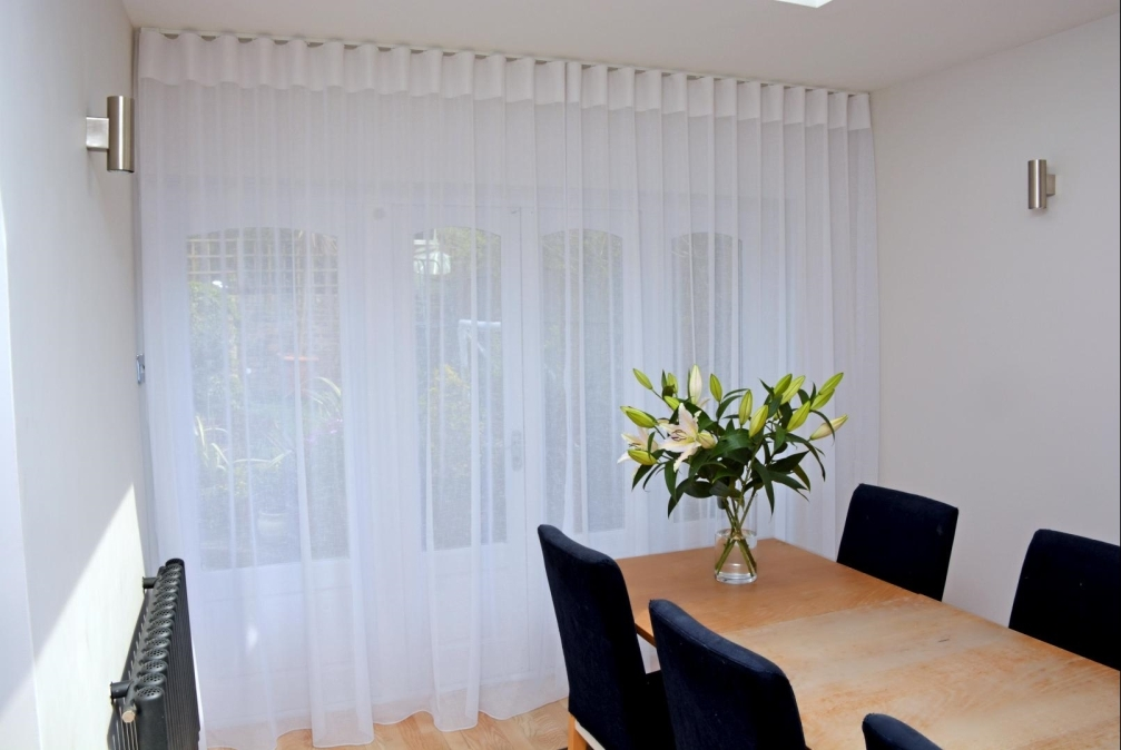 Close up of sheer, easy wave curtains. Wooden table with upholstered blue chairs and vase of blooming lilies.