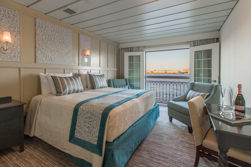 Bedding tucked. Wrinkles minimized. Use only props - champagne & glasses - provided or available to all guests. Windows open for full outside (river cruise) view.