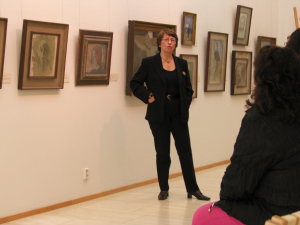 Sue Cedercreutz speaking about Helene Schjerfbeck in front of her paintings at Villa Gyllenberg art museum.