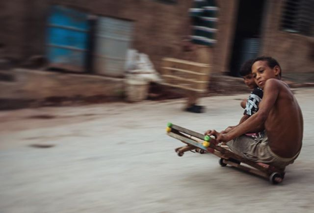Children racing down a hill in Trinidad, Cuba. Their selfmade skateboards consist of wooden planks and obsolete ballbearings.