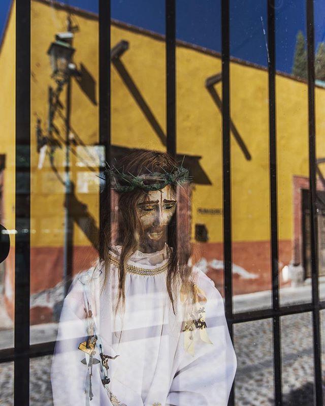 A Jesus statue in a shop window in San Miguel de Allende, relecting the street across.