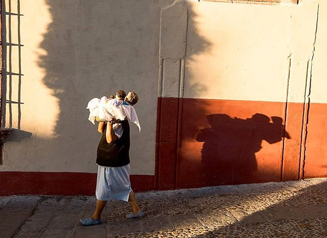 An elderly woman carrying baby dolls to a nearby church in San Miguel de Allende, Mexico. These very artistically crafted baby dolls are being used as lucky charms to pray for children in the family.
