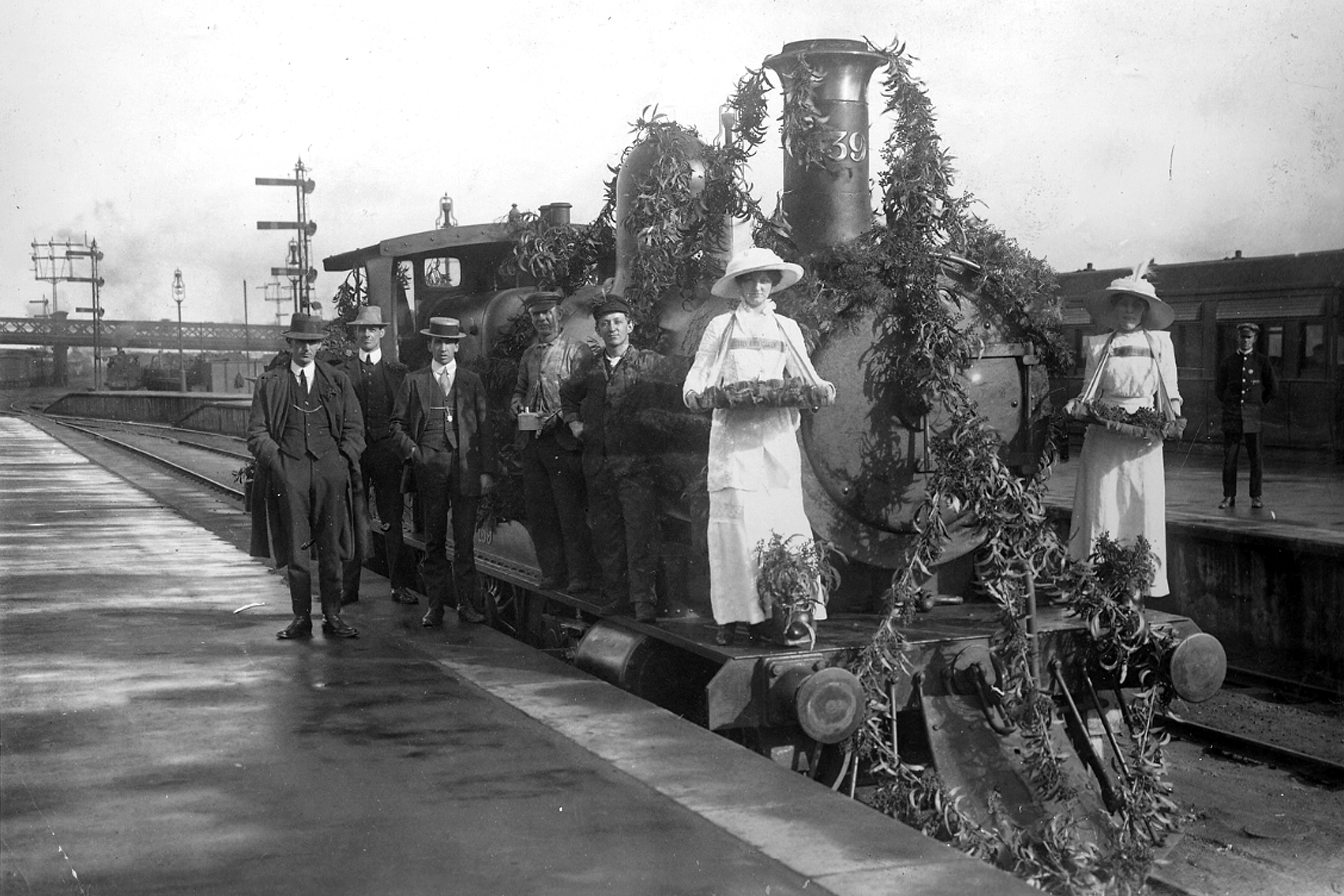 Wattle badge sellers with a locomotive decorated with wattle for Wattle Day, Adelaide, 1913. Image courtesy of the State Library of South Australia, PRG 280/1/7/249.