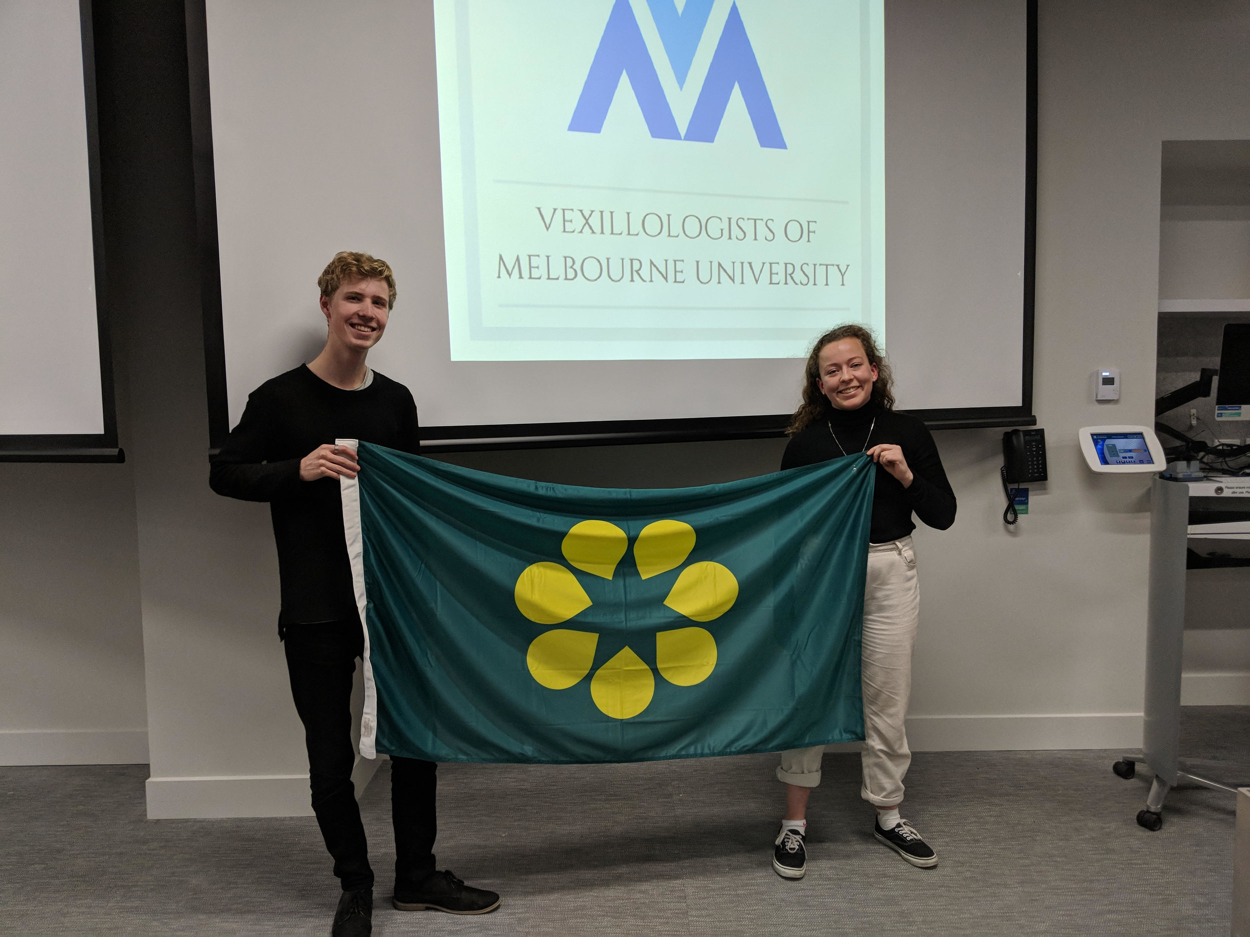 The President and Secretary-General of the Vexillologists of Melbourne University (VoMU) showing their support for the Golden Wattle Flag.