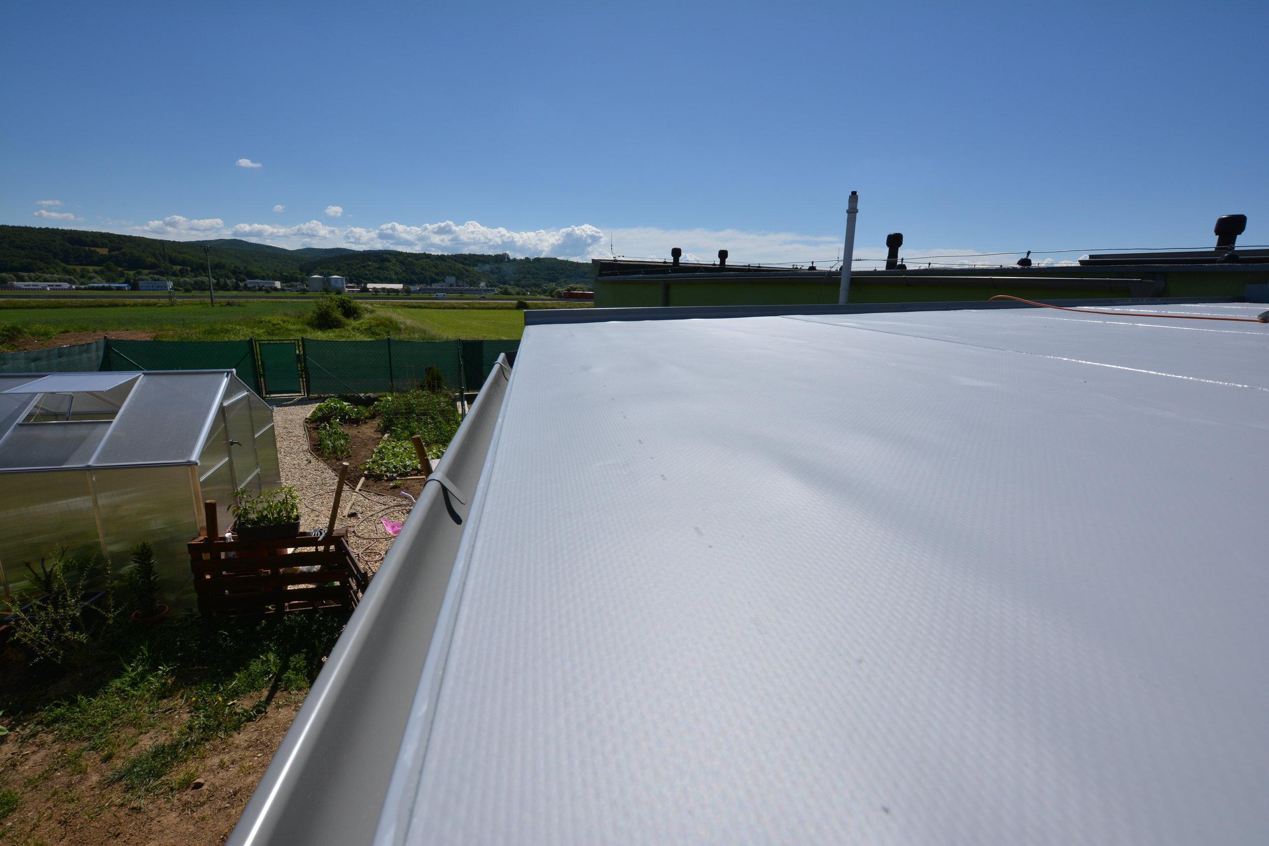 Detail ukončenia plochej strechy a žľabu.   Prístrešok na auto pri dome