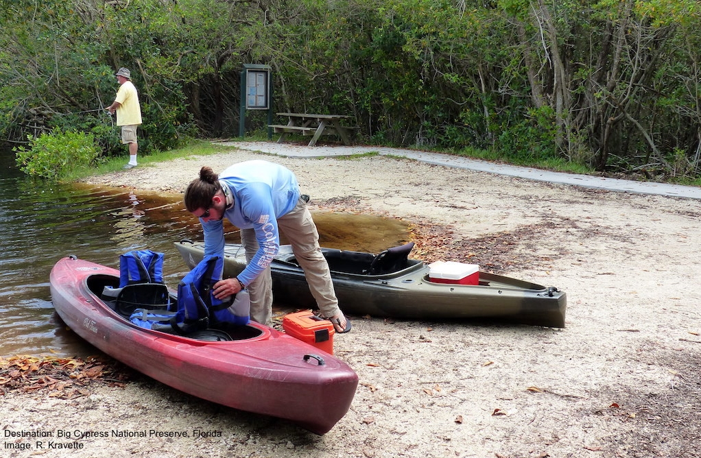 LOGAN GETTING THE KAYAKS READY, SEEING THE RELAXED FISHERMAN ON THE BANK EASED MY ALLIGATOR CONCERNED MIND. IMAGE. R. KRAVETTE