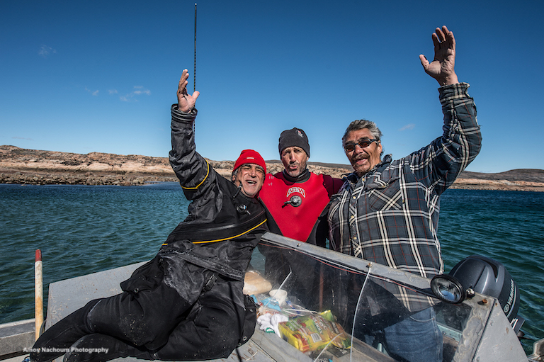 WILDLIFE PHOTOGRAPHER AND HOLDER OF THE DREAM, AMOS NACHOUM, WITH CO-PRODUCER, ADAM RAVETCH AND INUIT TRIBE LEADER & TOP GUIDE JOE KALUCACK, WHO PROVIDED KNOWLEDGE, WISDOM, AND HELP TO THIS AND NUMEROUS ARCTIC EXPEDITIONS, CELEBRATE THE SAFE AND HARMONIOUS CONCLUSION OF DIVING WITH POLAR BEARS. IMAGE: COURTESY OF ©AMOS NACHOUM PHOTOGRAPHY.