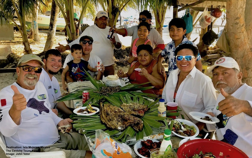 "GOOD FUN, GOOD FOOD, GOOD FAMILY! CO-FOUNDERS JOHN VATER AND CAPTAIN LOUIS ""CUCO"" AGUIRRE SHOW THUMBS UP WITH THEIR WIVES ADRIANA AND ELENA, SON JESUS, JOHN'S NEPHEW ANDRE AND THE KIDS AT A MULTY-GENERATIONAL, INTERNATIONAL CEVICHE FAMILY MEAL. IMAGE: THANKS TO JOHN VATER AND CEVICHE TOURS"