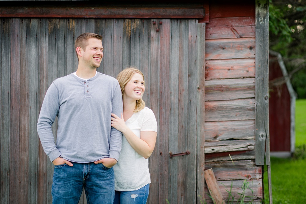 Couple looking away in front of old barn wood | Outdoor, country styled engagement session near Audubon, MN | Amer Langerud Photography