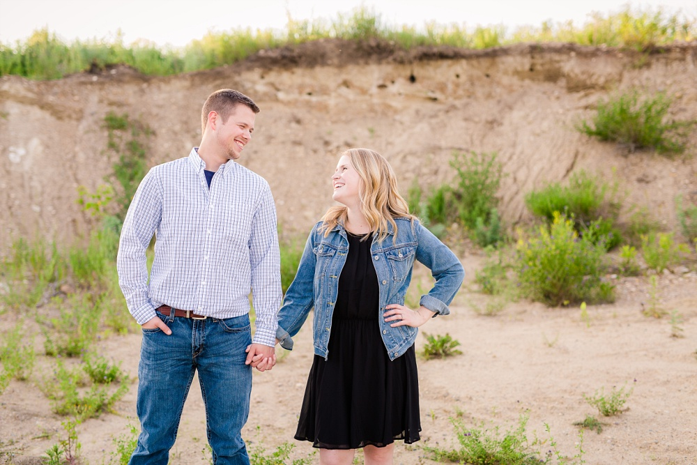 Couple standing, holding hands in gravel pit | Outdoor, country styled engagement session near Audubon, MN | Amer Langerud Photography