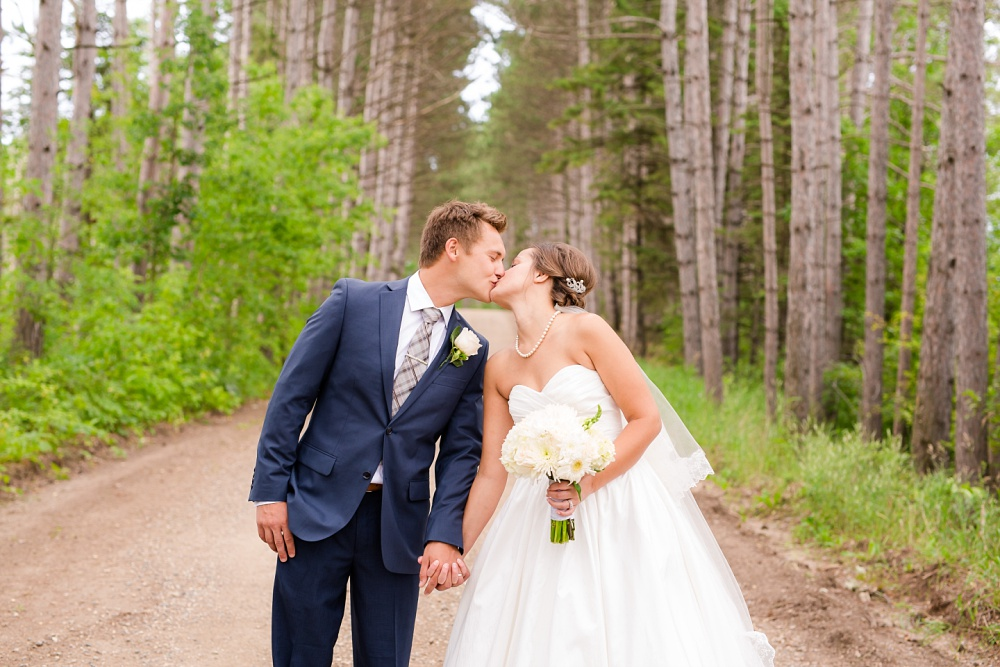 Wolf Lake, MN Country Styled Wedding, White Dress, Blue Suite | Photographed by Amber Langerud Photography | Bride & Groom Kissing by ponderosa pine trees