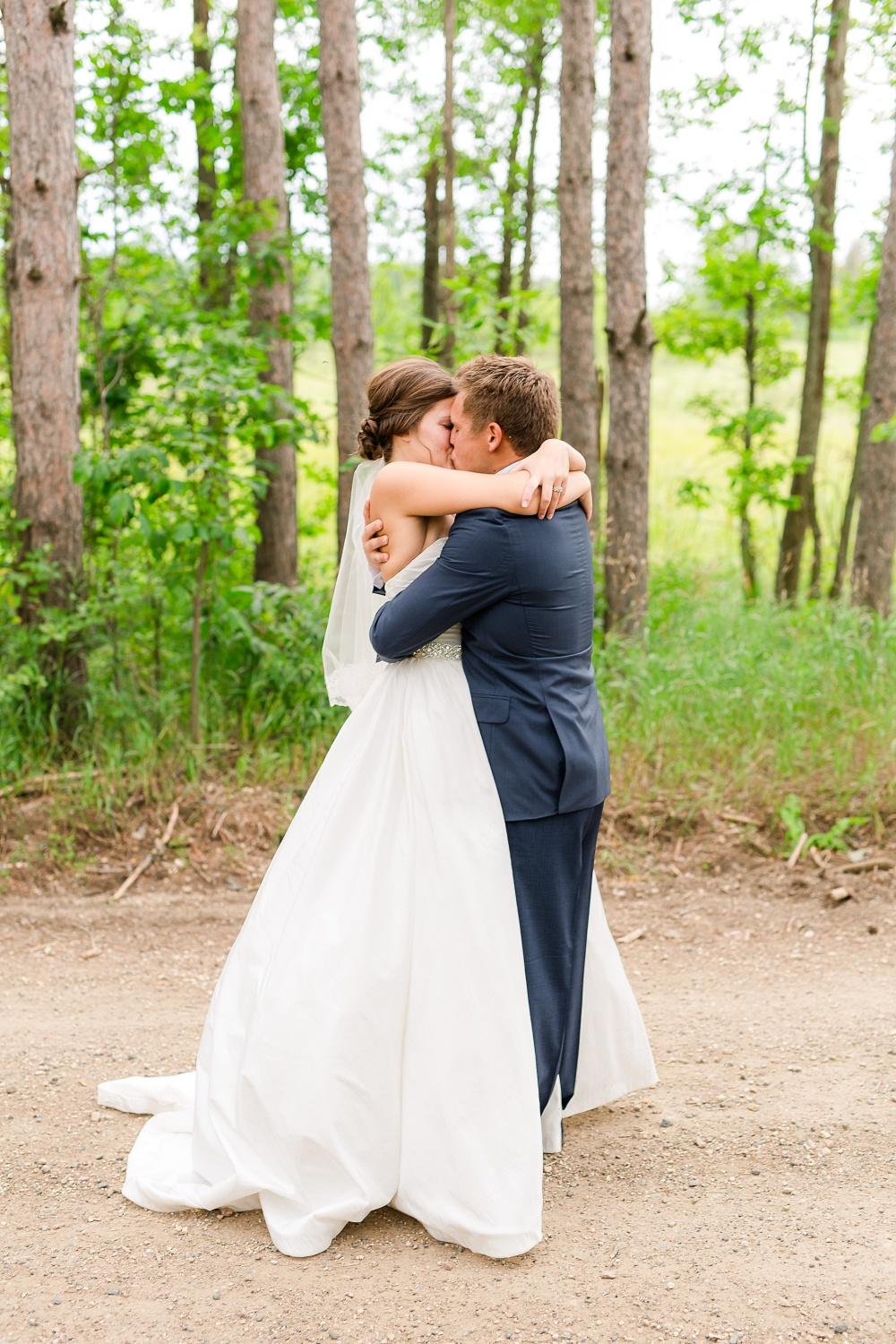 Wolf Lake, MN Country Styled Wedding, White Dress, Blue Suite | Photographed by Amber Langerud Photography | Bride & Groom embracing each other kissing