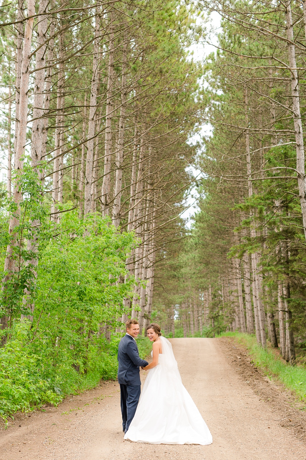 Wolf Lake, MN Country Styled Wedding, White Dress, Blue Suite | Photographed by Amber Langerud Photography | Bride & Groom Looking Back at Camera