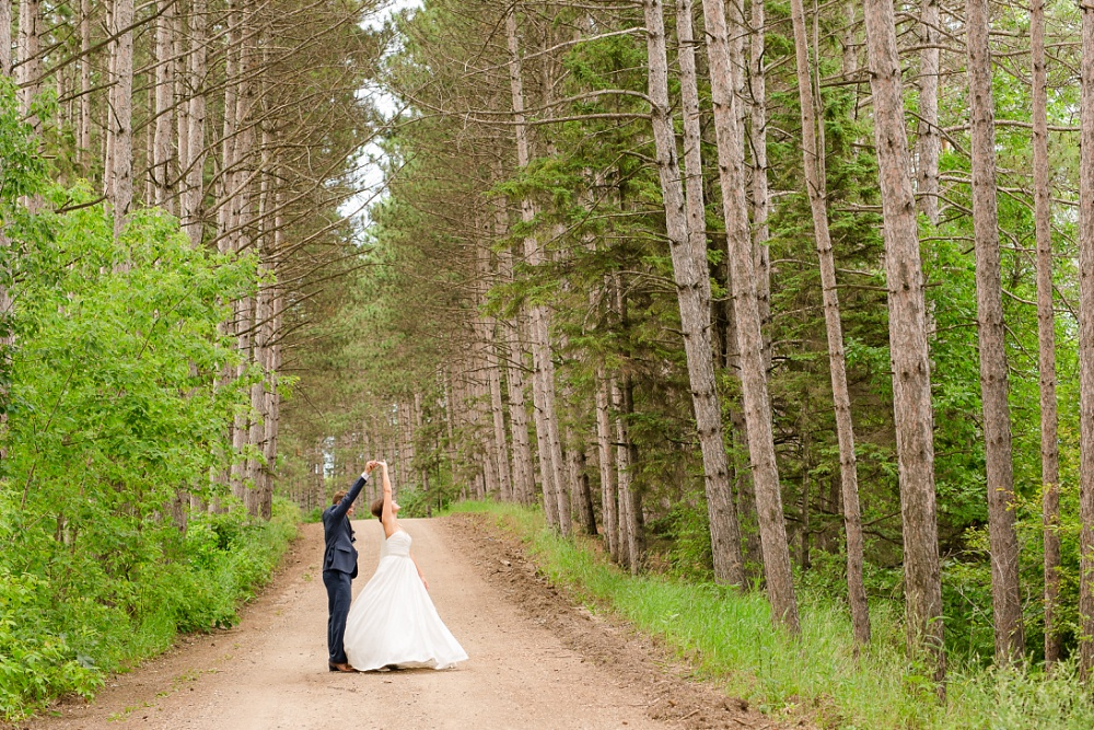 Wolf Lake, MN Country Styled Wedding, White Dress, Blue Suite | Photographed by Amber Langerud Photography | Groom twirling the bride