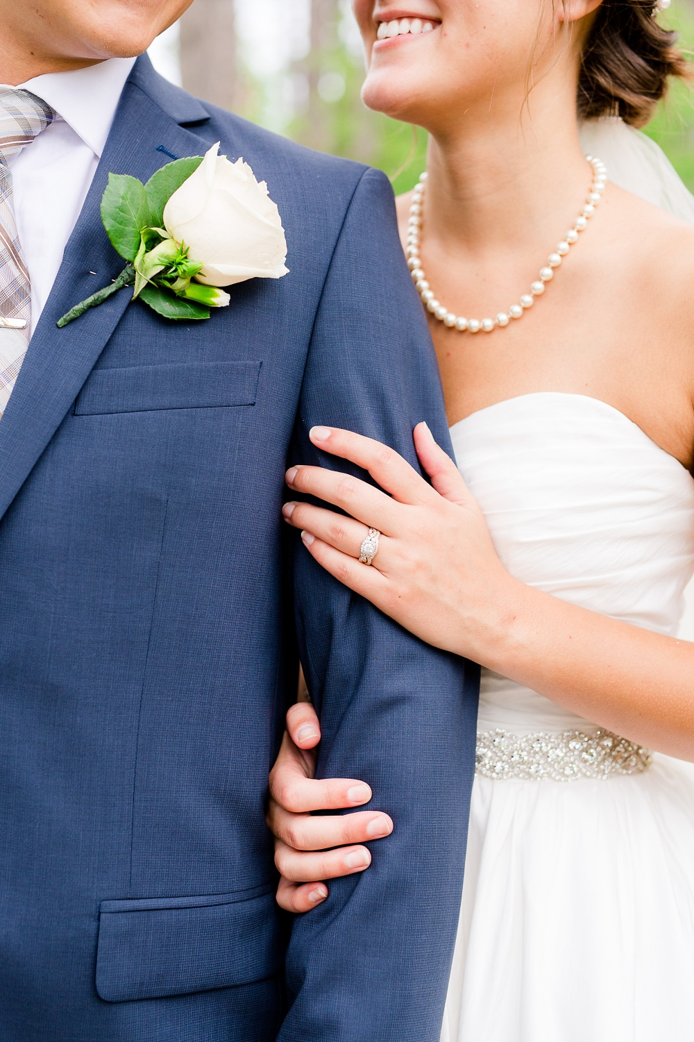 Wolf Lake, MN Country Styled Wedding, White Dress, Blue Suite | Photographed by Amber Langerud Photography | Close-up details of bride's hands and wedding ring
