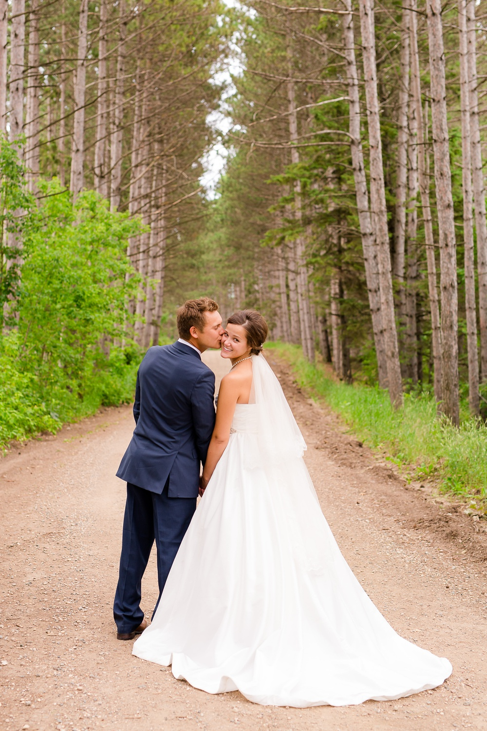 Wolf Lake, MN Country Styled Wedding, White Dress, Blue Suite | Photographed by Amber Langerud Photography | Groom Kissing Bride's Cheek