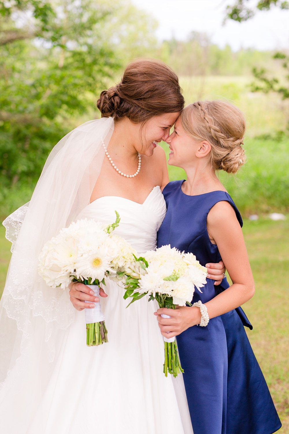 Wolf Lake, MN Country Styled Wedding, White Dress, Blue Suite | Photographed by Amber Langerud Photography | Bride & her Niece bridesmaid