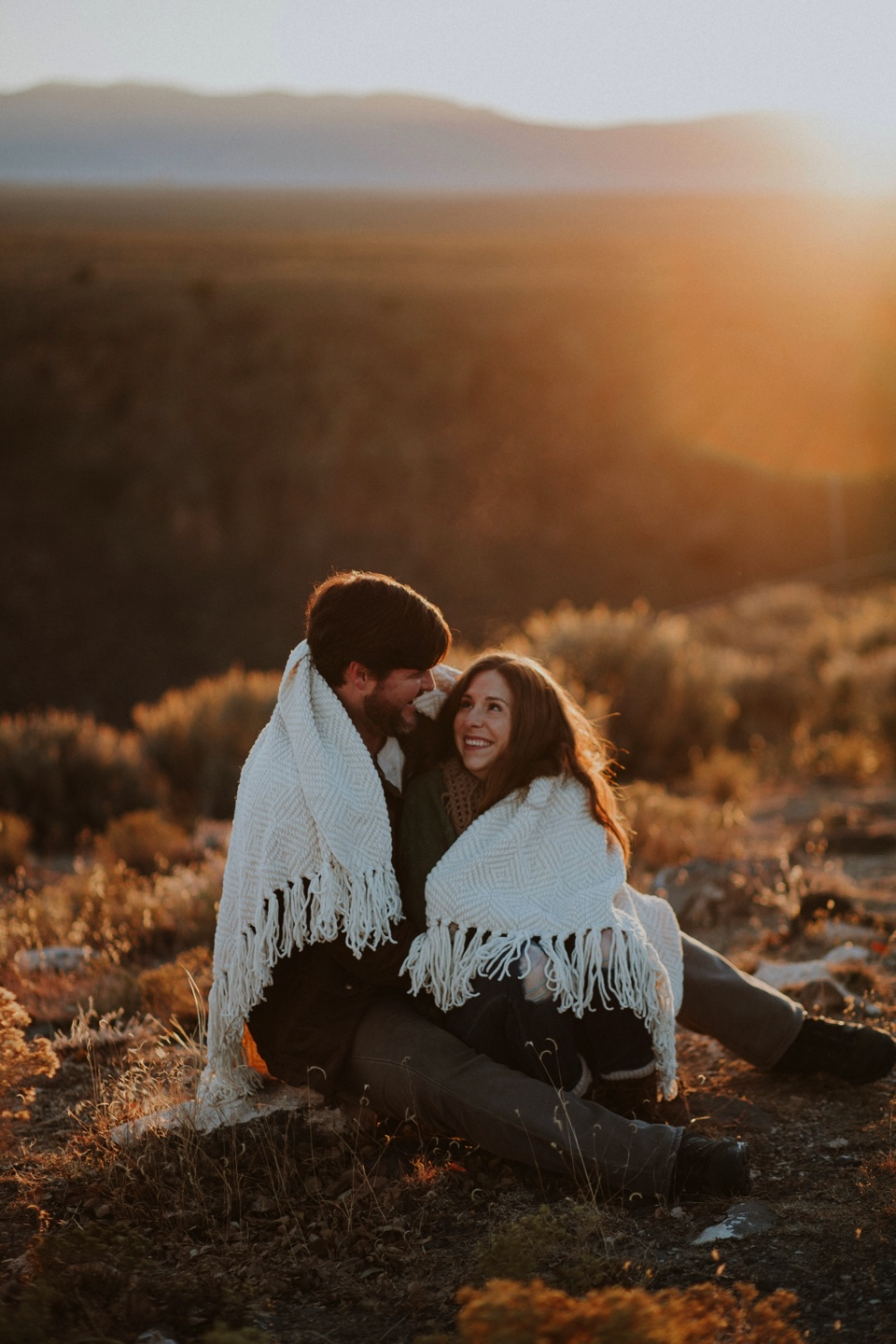 Natalie and Boots traveled all the way from the sunshine state for their beautiful Sunrise Engagement Photos at the Rio Grande Gorge Bridge in Taos, New Mexico. It was a chilly morning in Taos and we were all pretty frozen! It was 6 degree weather when we met at the Rio Grande Gorge Bridge, but there is nothing in the world like seeing the sun rise at the gorge bridge in Taos. The golden light and cotton candy skies from the sunrise were absolutely gorgeous! Natalie and Boots had the perfect winter engagement outfit inspiration for these chilly sunrise engagement photos.