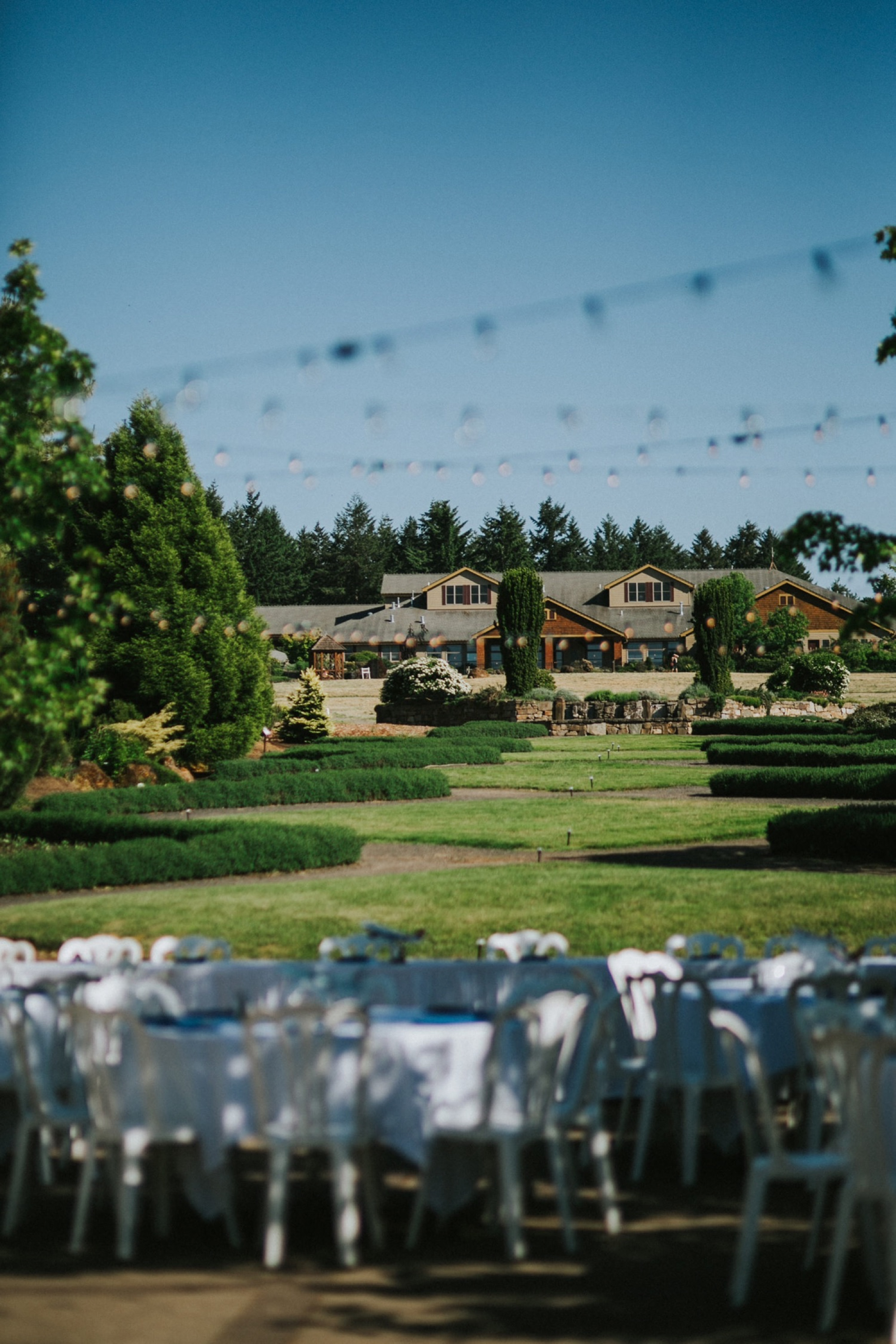 Daniel and Jeremy had a truly enchanting and magical wedding at  The Oregon Garden Resort  in Silverton, Oregon. It was truly beyond stunning from decor to scenery to each beautiful moment throughout the entire day. Along with the fabulous scenery including all of the greenery and fresh florals in bloom, the decor and theme Daniel and Jeremy chose for their special day was seriously SO COOL. Daniel and Jeremy are both flight attendants so the theme for their big day was travel (and of course, airplanes!). The blue tones and travel themed decor was the perfect mix of elegance and quirk.