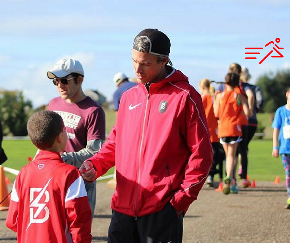 Bowerman TC pro coach Jerry Schumacher (right) offers words of encouragement to a young harrier.