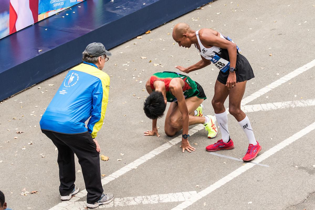 2015 NYC Marathon, Meb comforting a defeated Yuki   photo © kevmofoto.com