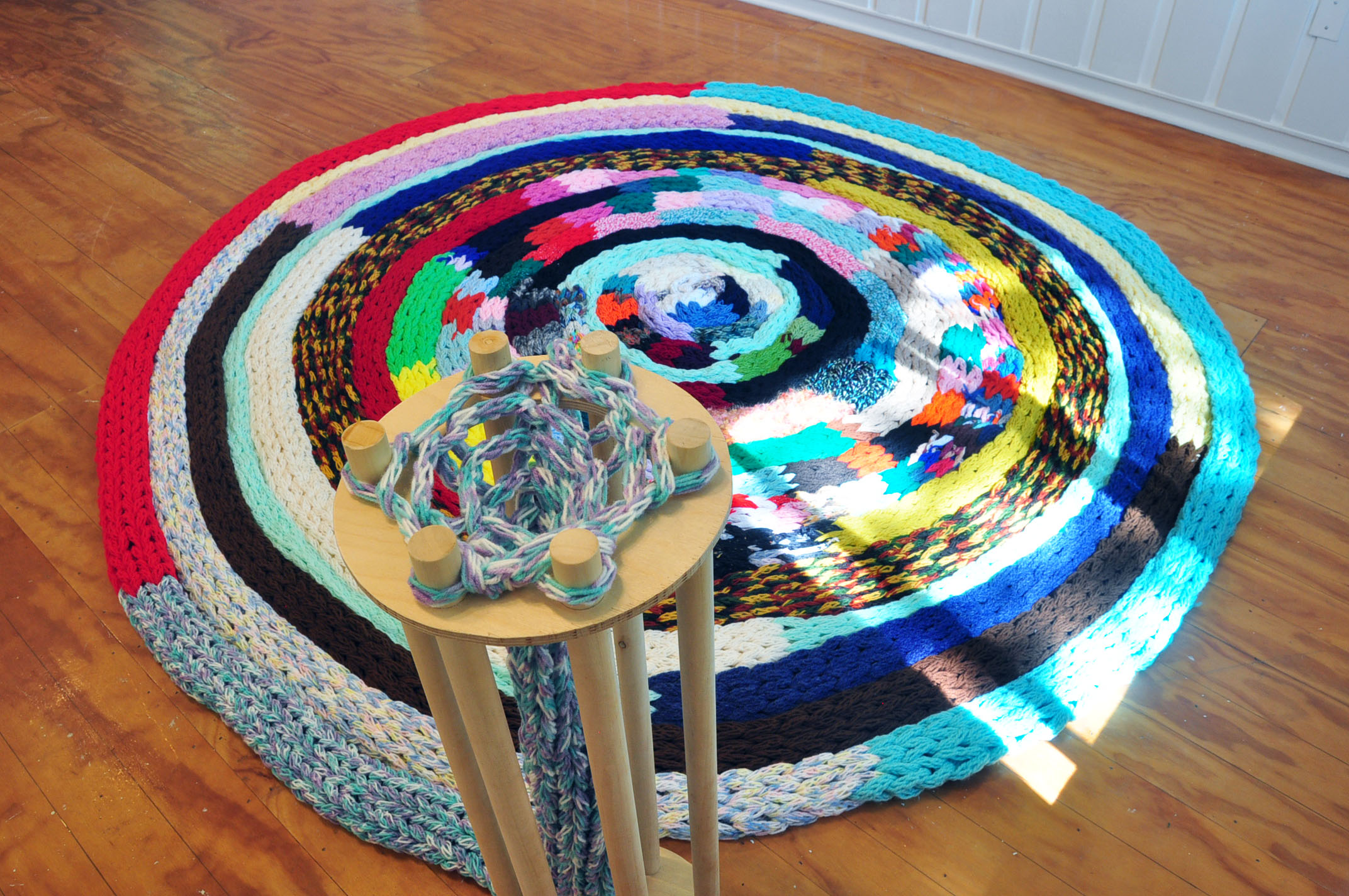 The Machine: Knitting Ouroboros , 2019, yarn, wood, approx. 10ft Wide in Diameter