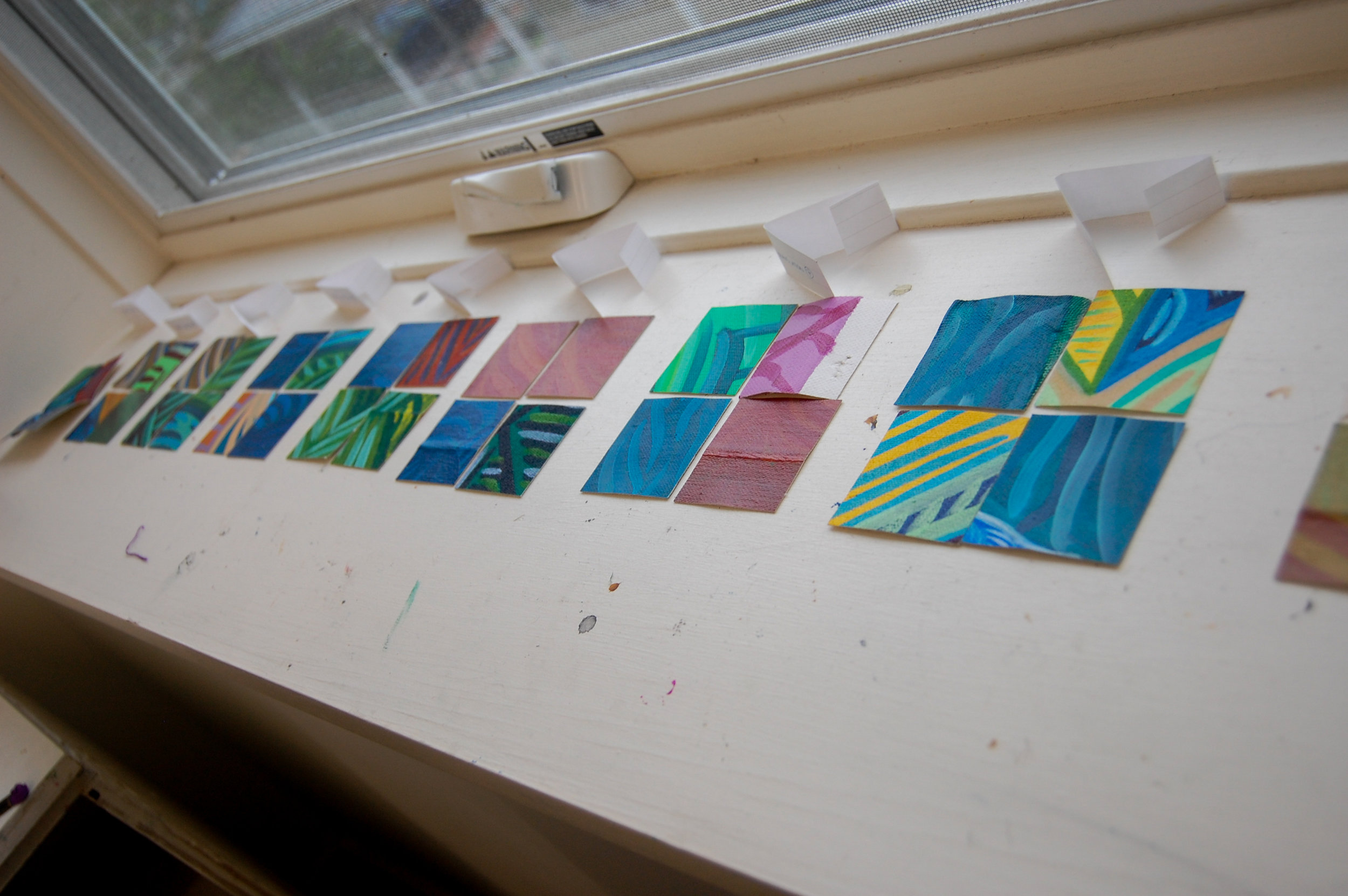 Translation Series  paintings pre-planned and laid out on a window sill.