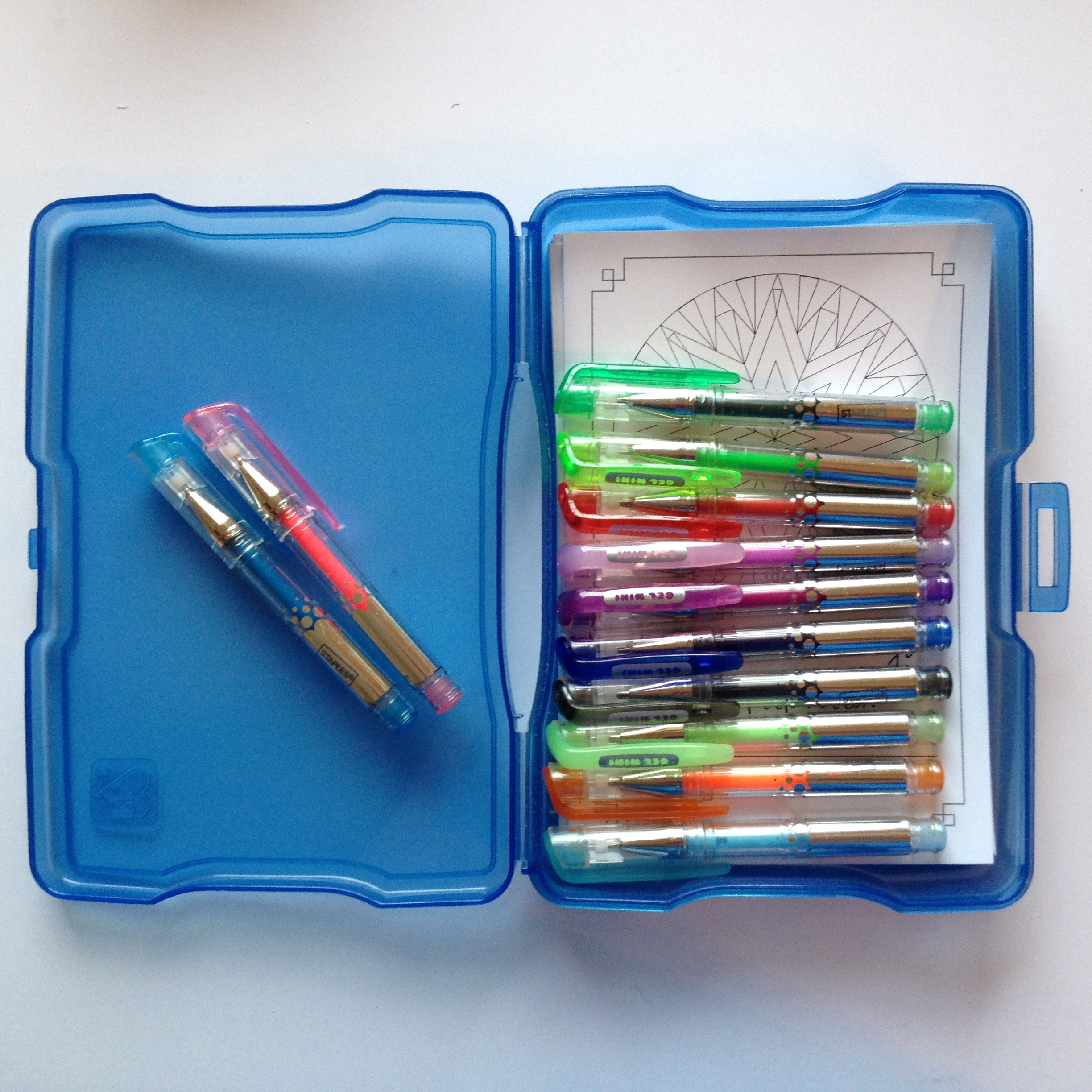 The mini-gel pens shown in an open plastic photo storage case. Mandala cards (shown behind the pens) fit nicely behind the pens, to make a handy, self-contained colouring kit.