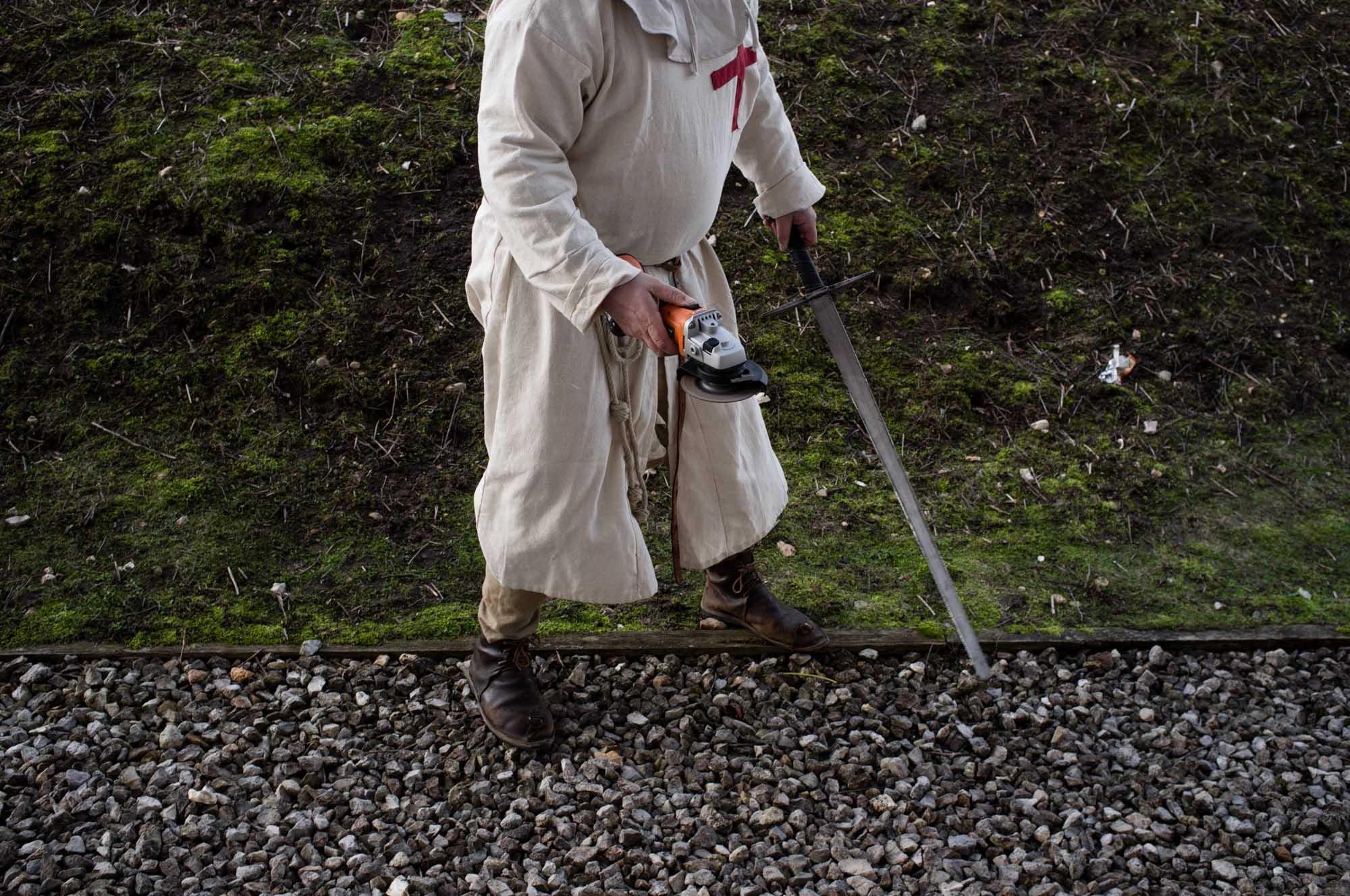 Un combattant habillé en costume de templier émousse son épée à deux mains pour qu'elle ne soit pas tranchante.