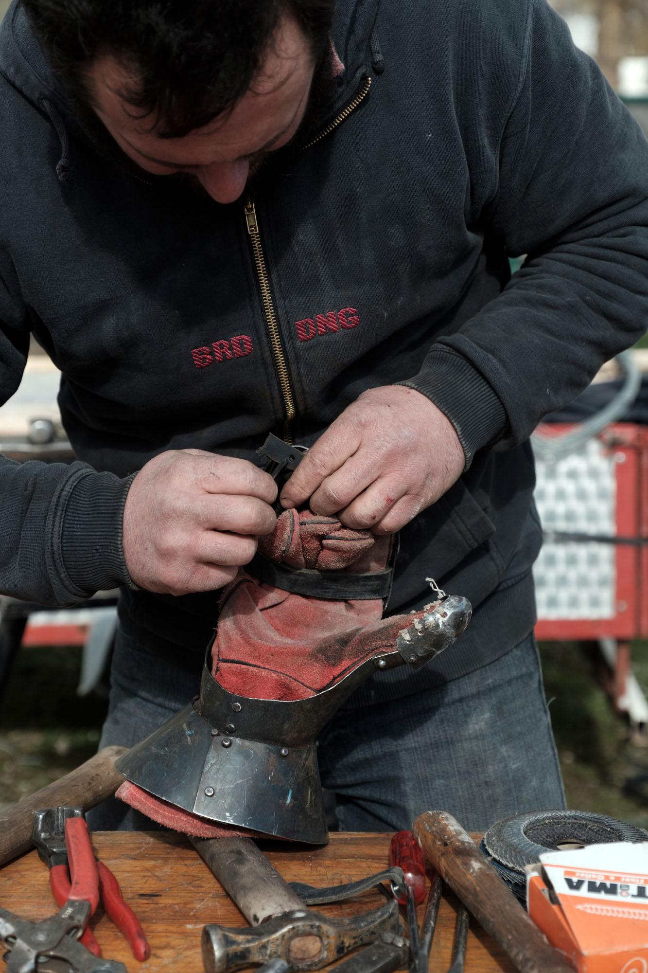 Un artisan répare une armure qui a été endommagée pendant un combat. Village médiévale de Saint Dizier pendant le championnat de France. Mars 2019.
