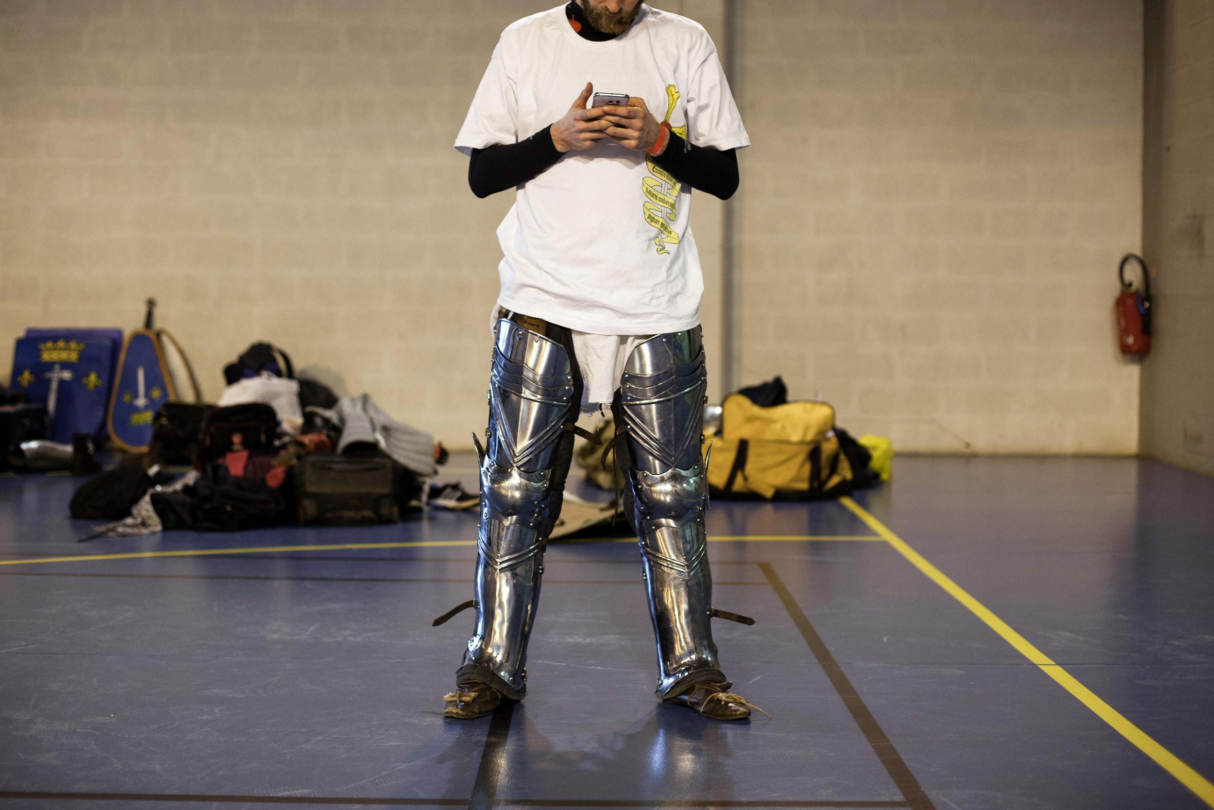 Un combattant regarde son téléphone avant le début du tournoi en duel. Carrière sous Poissy. (Région parisienne)