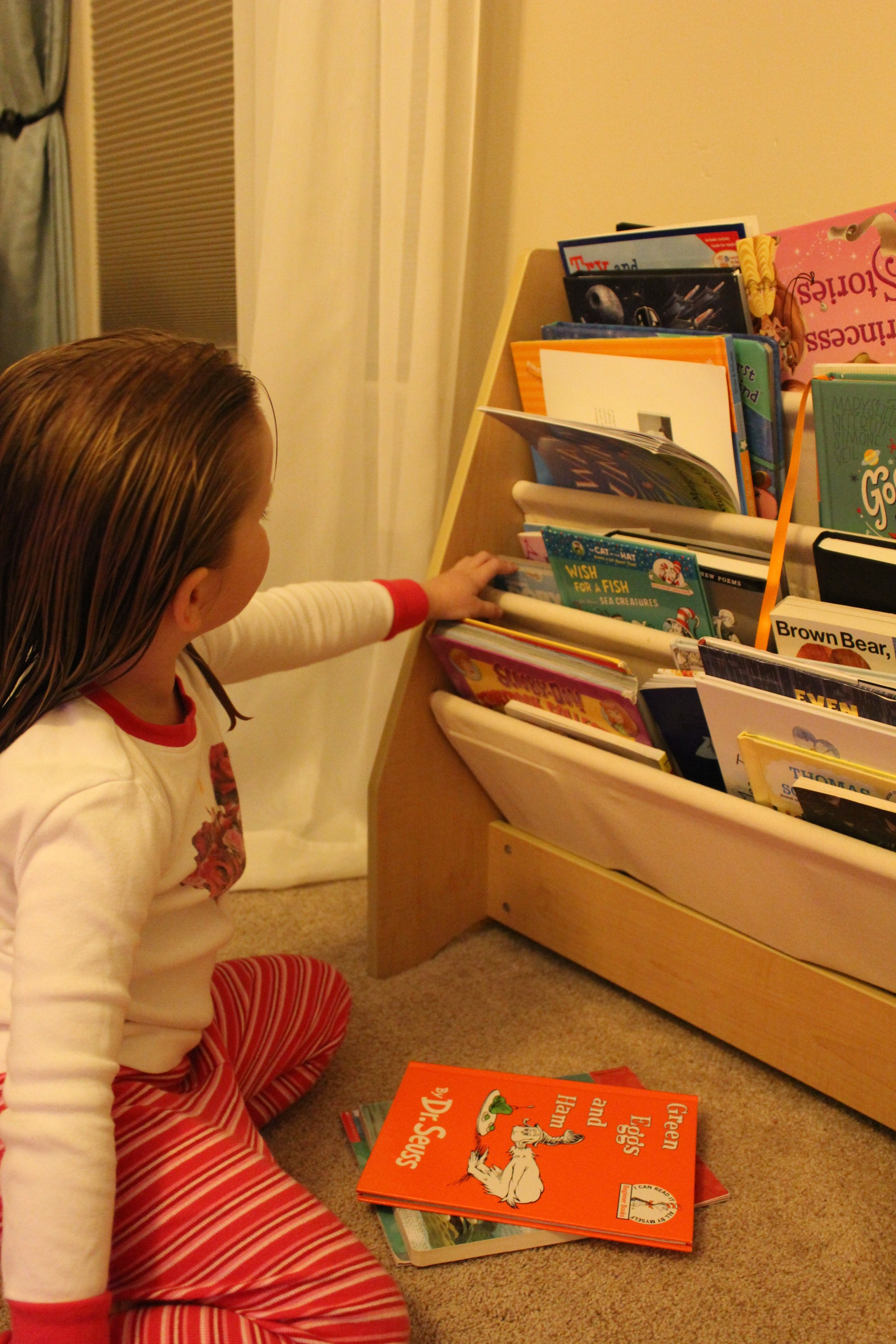 Addie going through her bookcase, selecting books to donate.