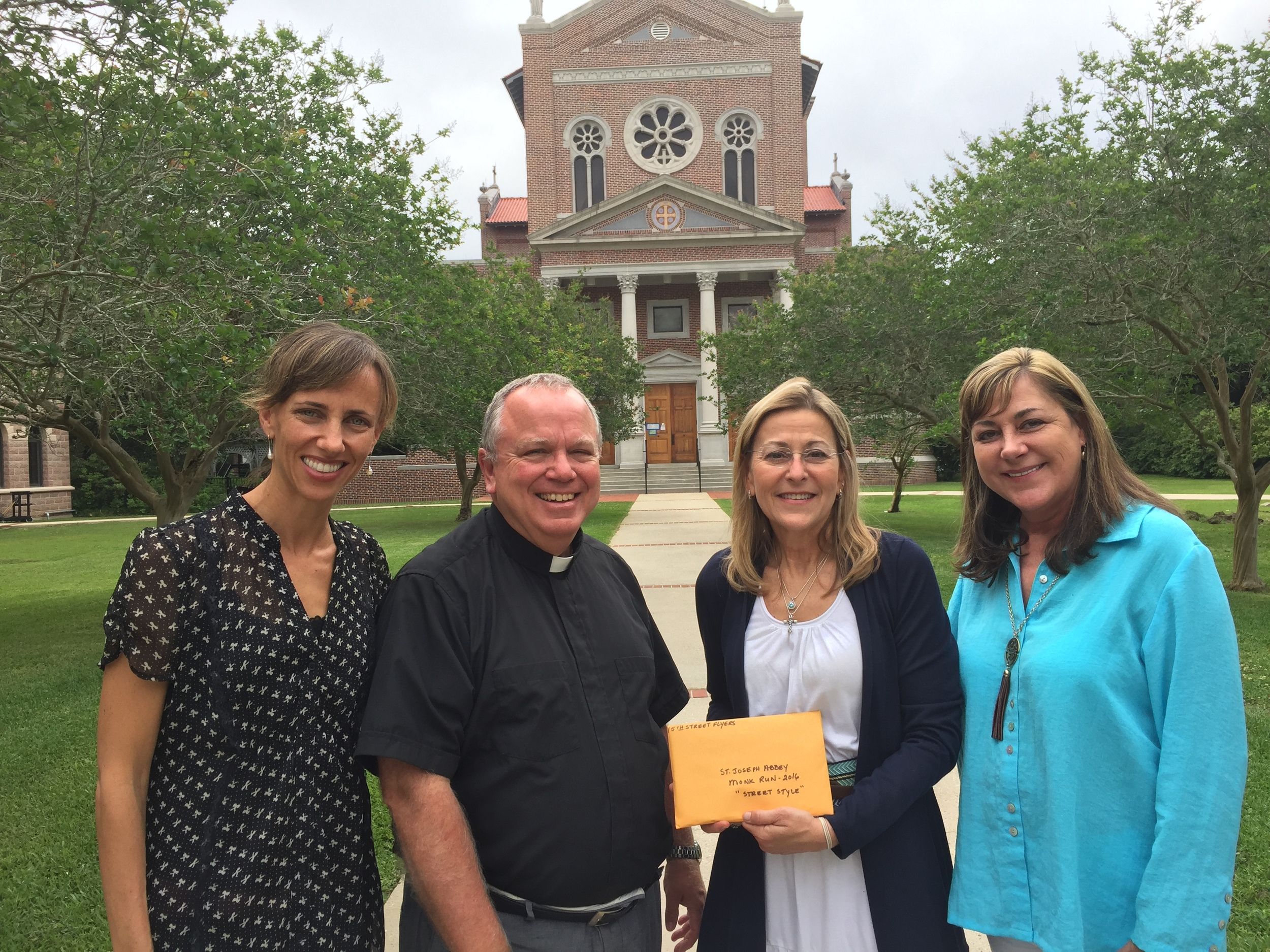 Abbot Justin Brown, O.S.B., is presented with a check for $7,815 from this year's Monk Run by Diane Weiss of the 15th Street Flyers. Standing with Brown and Weiss are Leslie Tate, Director of Institutional Advancement for the Abbey and Kathy Nastasi, Manager of Marketing and Volunteers for the Abbey.