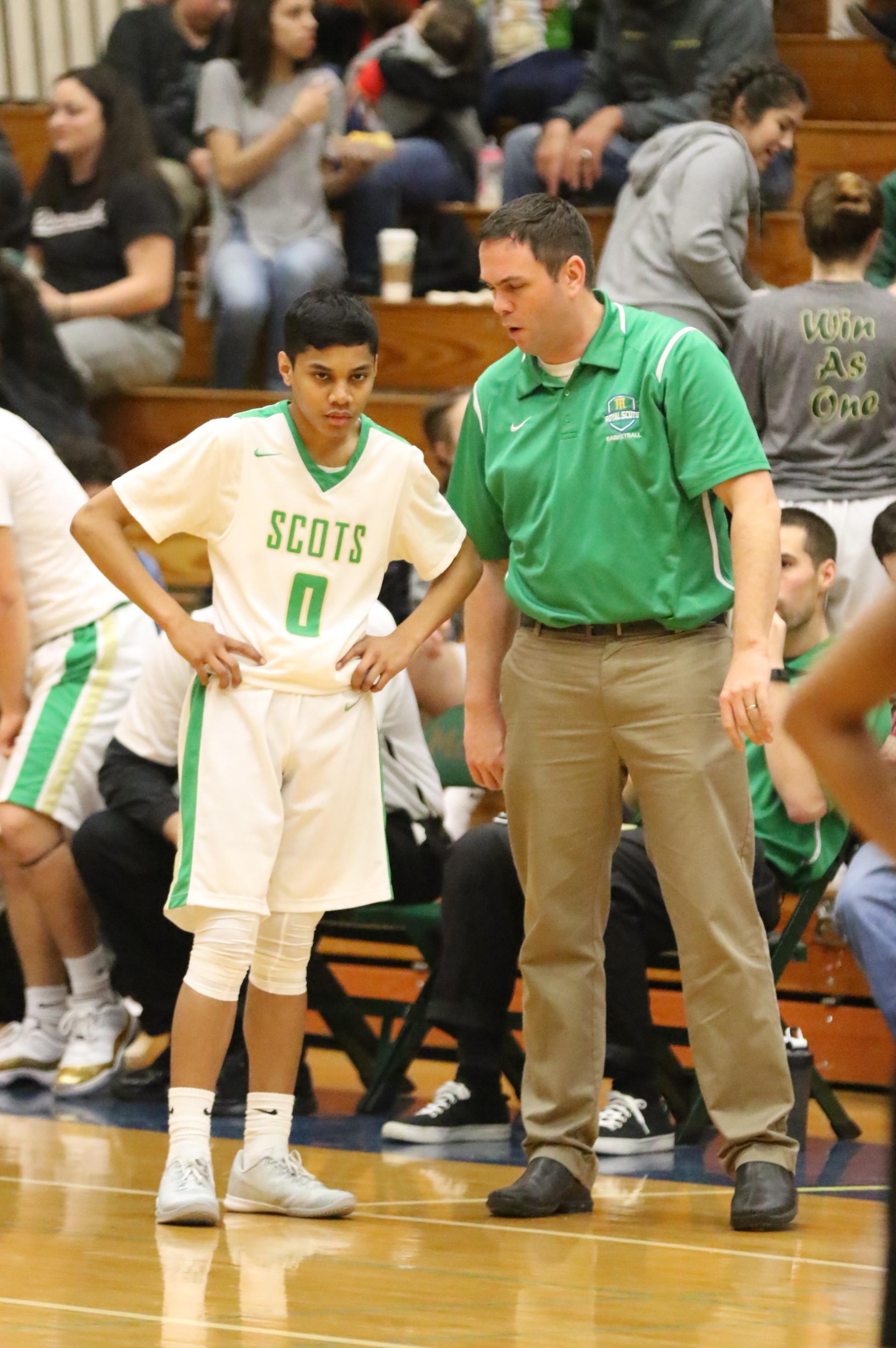 Coach Dean Sanderson gives Drioji a play to run. Photo by Kent Brewer.
