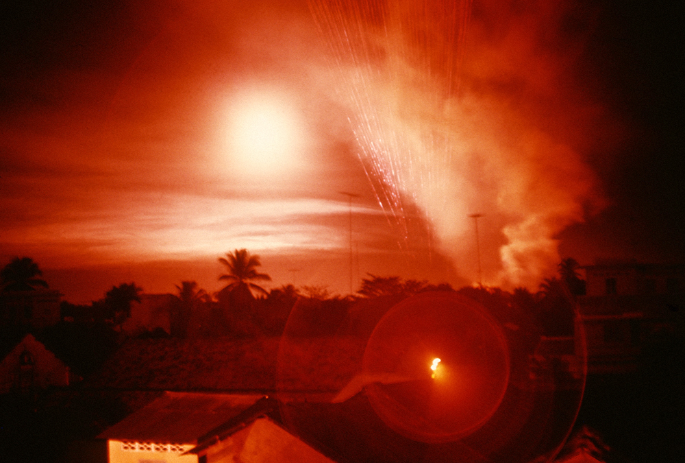 Tet Offensive, Saigon. Overhead a helicopter gunship fires 5,000 bullets a minute. Every fifth bullet is a red tracer that helps direct fire to its target.Vietnam, February 1968.jpg