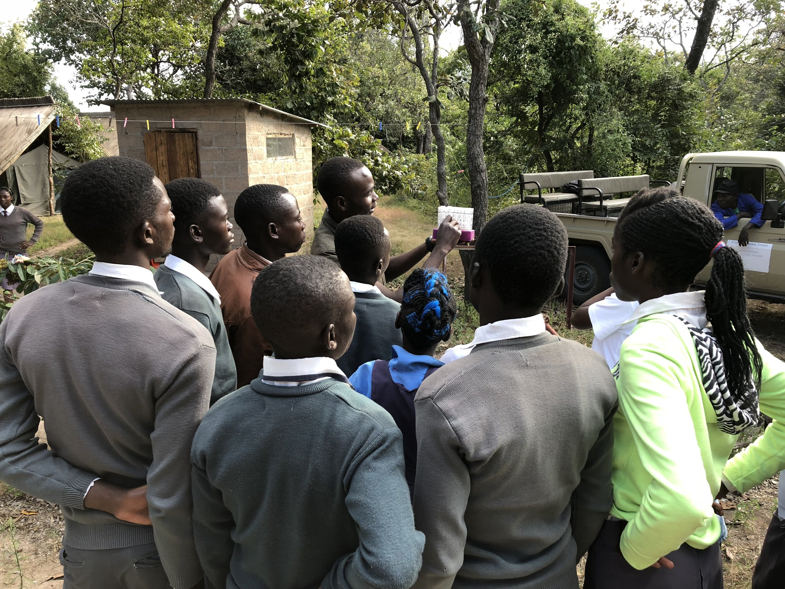 Simon Siame teaching students about collecting baboon fecal samples on a visit to Kasanka National Park, Zambia