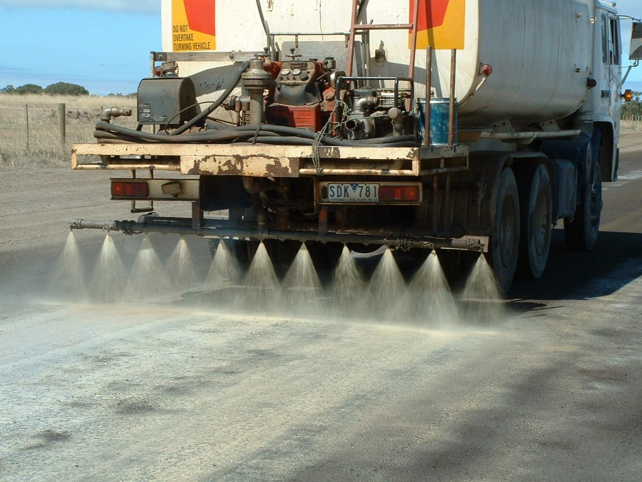 Road getting sprayed with Soilbond's dust control solution.