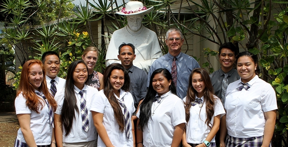 Mr. Carrasco (standing in front of the statue of St. Damien), Principal Br. Daniel Casey, teacher Elle Stricklen, and some of the students who were slated to attend the Mission Trip to Kalaupapa in 2015.