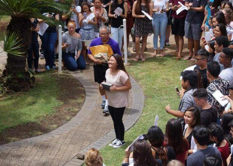 Senior class president Kim Aguada beams as she readies to place the 2016 class paver in the pathway.