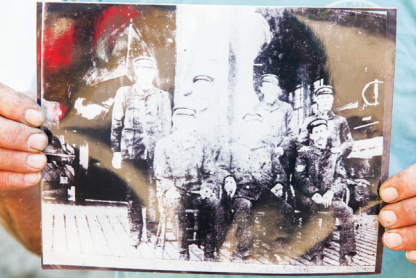 Hal Coste holds an age-worn image of his grandfather and his crew