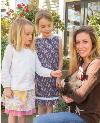 Lucienne and Stella Fletcher watch as Sydney Langley cuddles her mother's last remaining chicken.